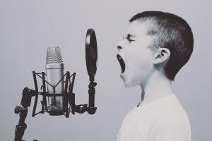 Kind singt in Mikrophon